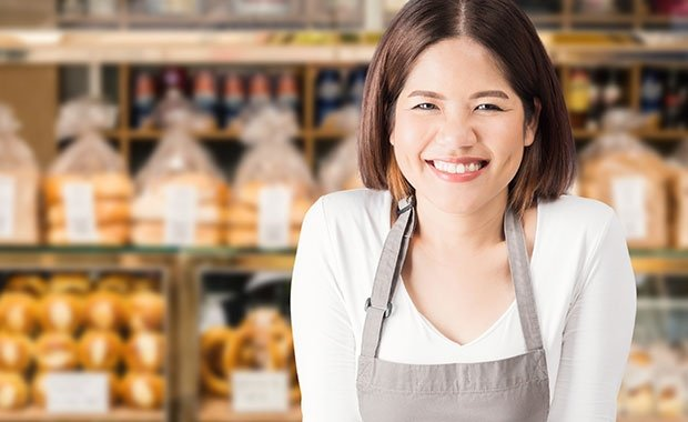 Female Business Owner With Bakery Shop Background