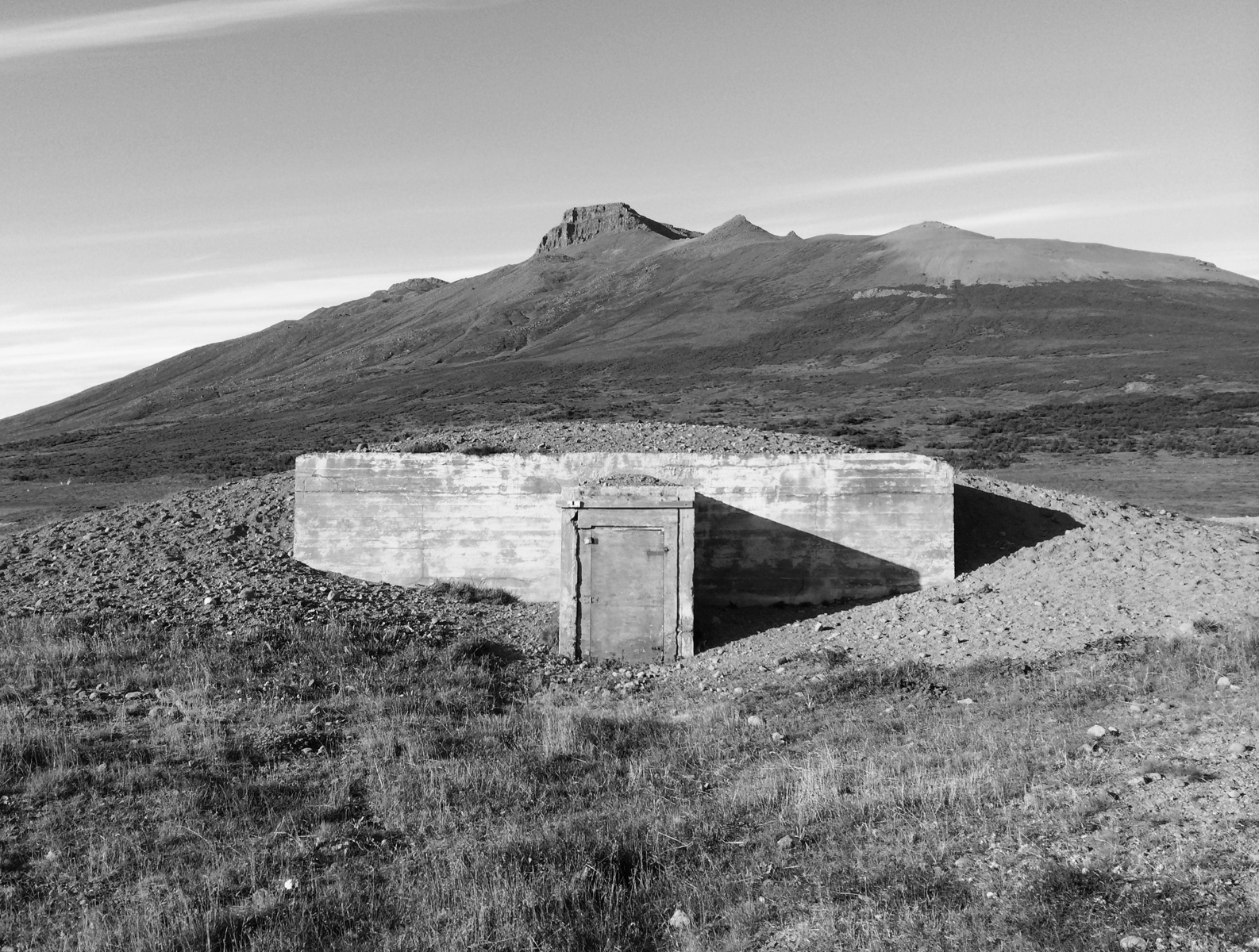 A lone, windowless concrete building, in the background a treeless mountain.