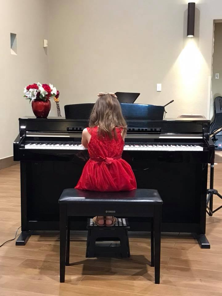 Little girl in red dress plays the piano