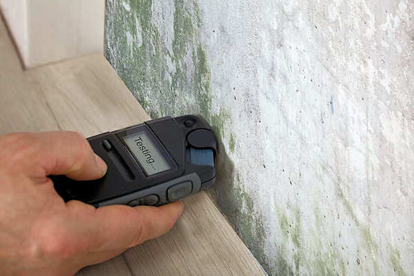 Using a moisture meter to check the moisture content of building material