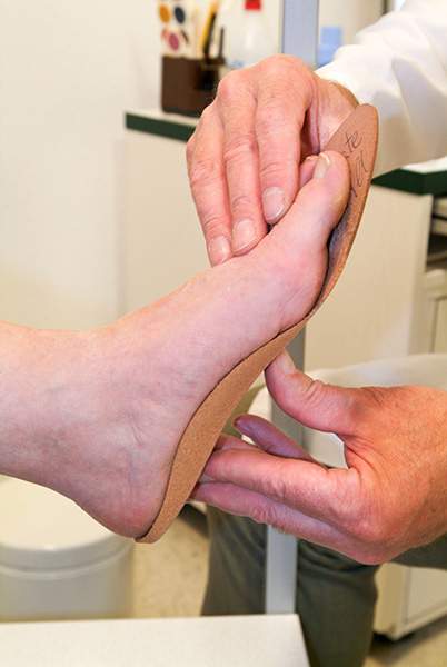 Foot being measured for orthopedic insoles