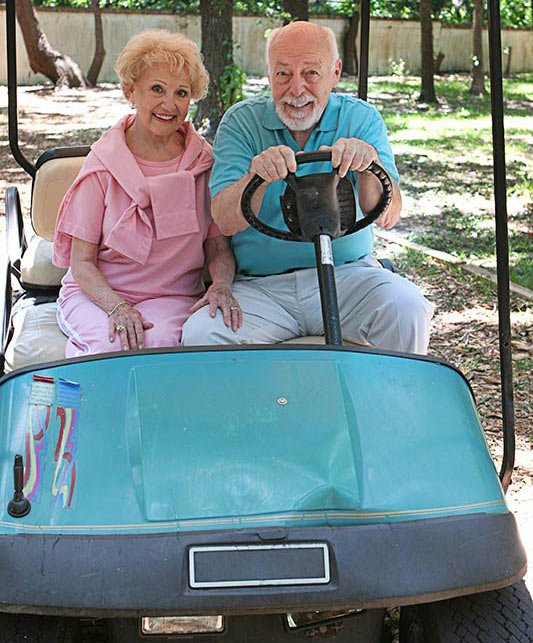 A senior couple in a golf cart