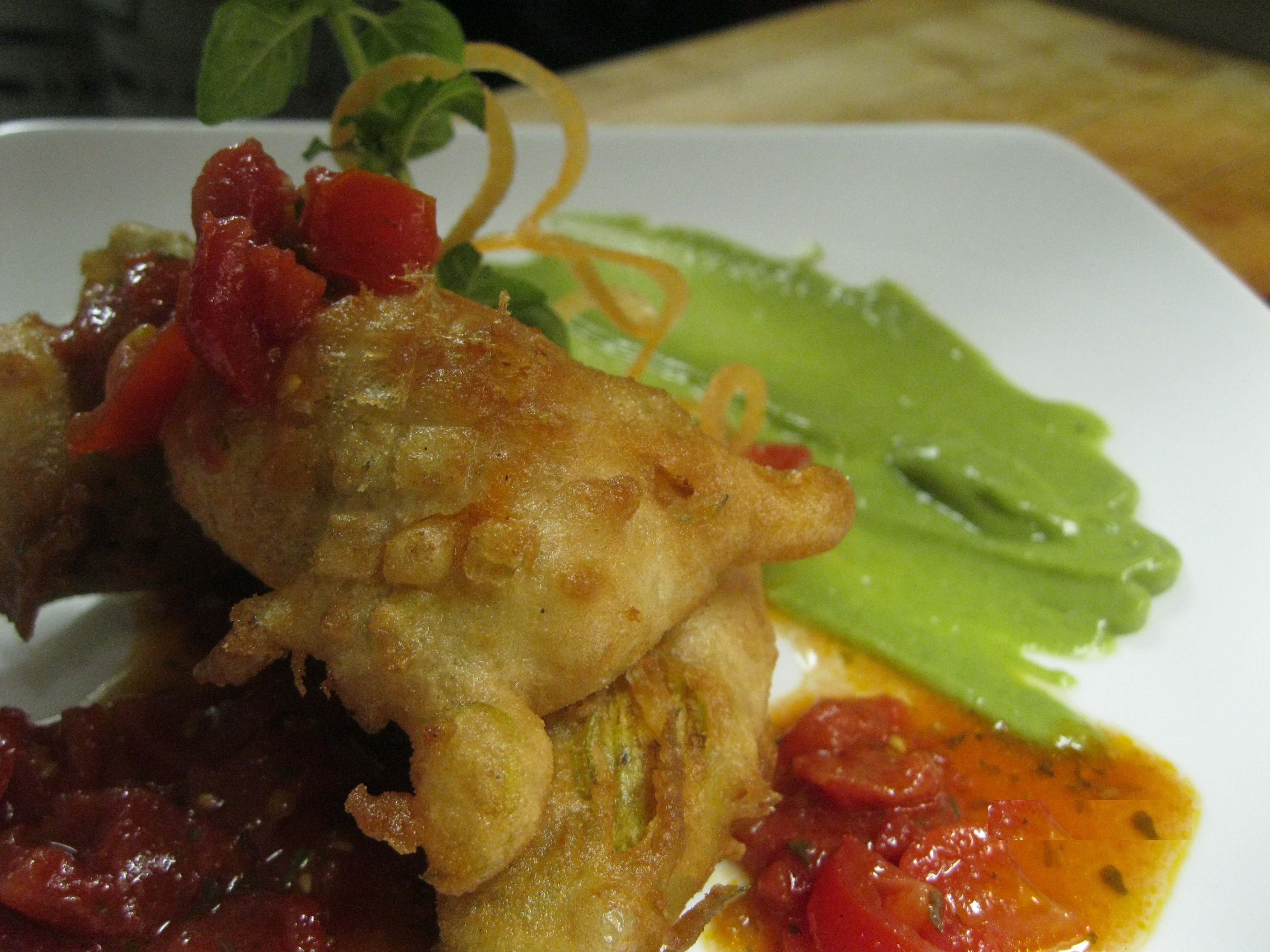crab stuffed  zucchini blossom with an avocado coulis and heirloom tomato concasse