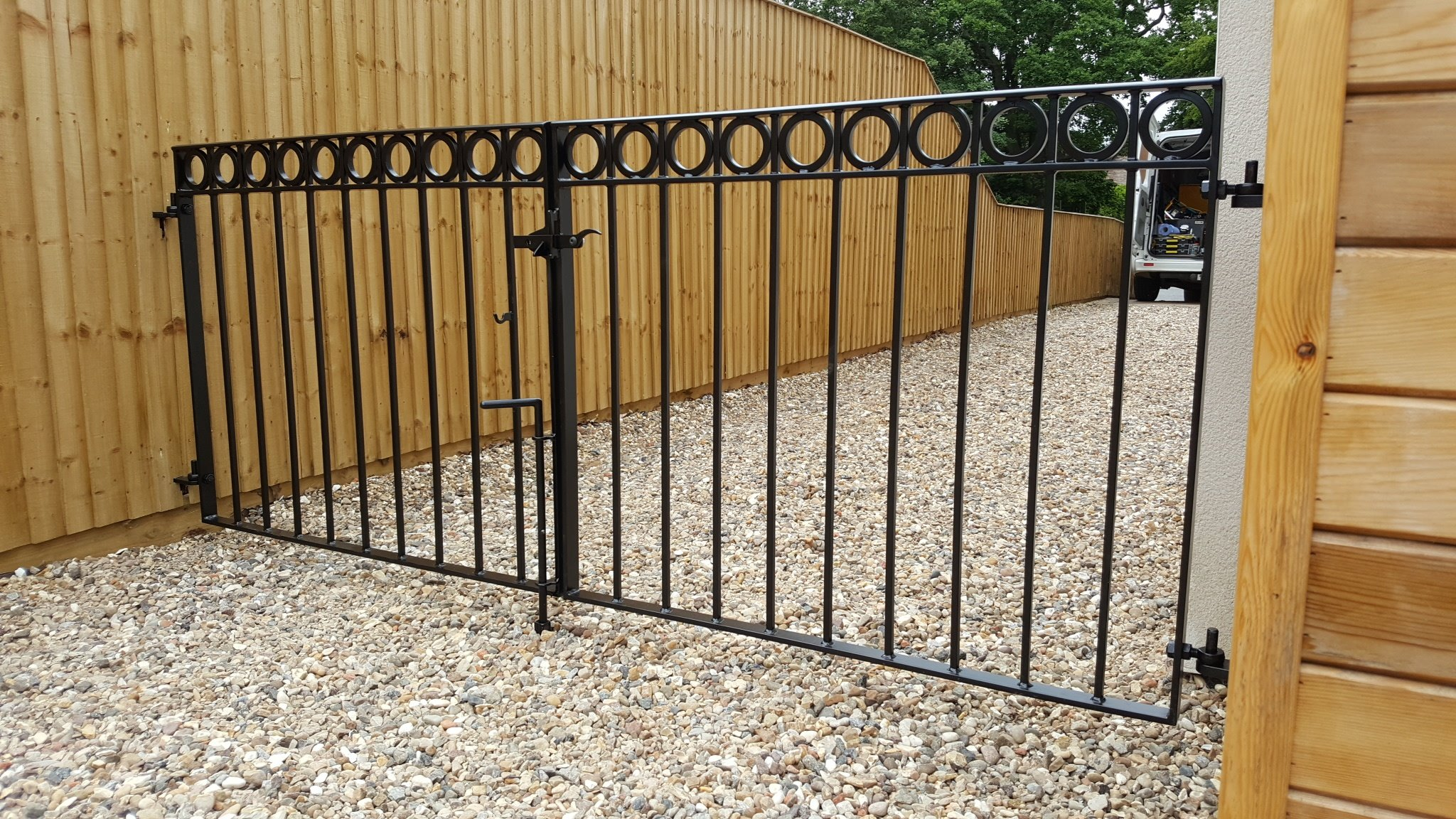 Simple, modern double drive gates with decorative rings & satin black powder coating.