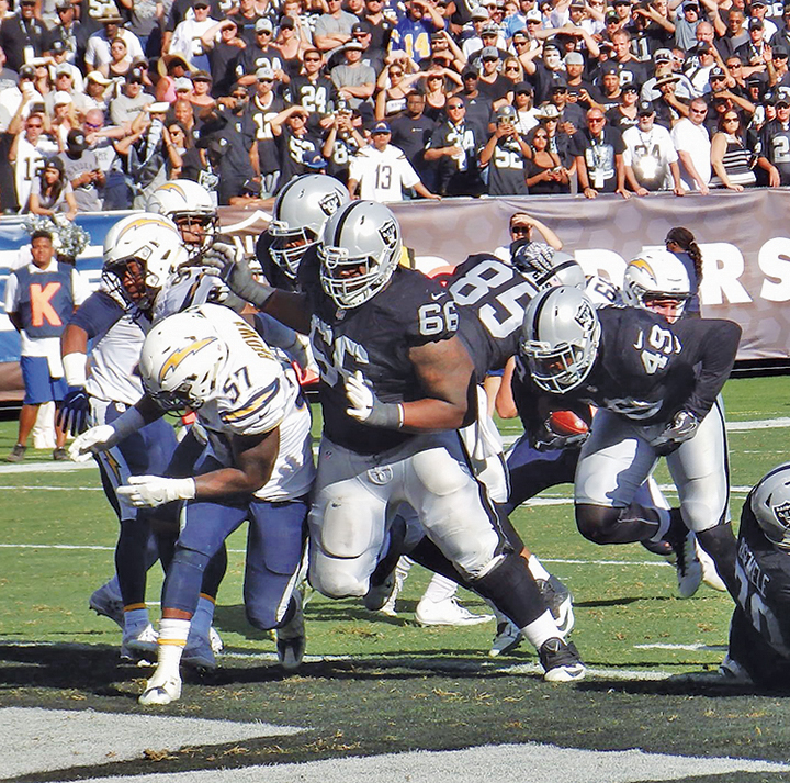 Oakland Raiders right guard Gabe Jackson clears a path for fullback Jamize Olawale for a fourth-quarter touchdown to put the Raiders ahead 34-24. Oakland beat the Chargers 34-31 for their first home win of the season and a 4-1 record.