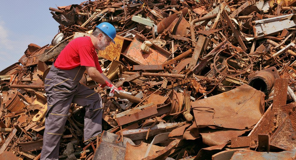 Worker At Heap Of Old Scrap Metal