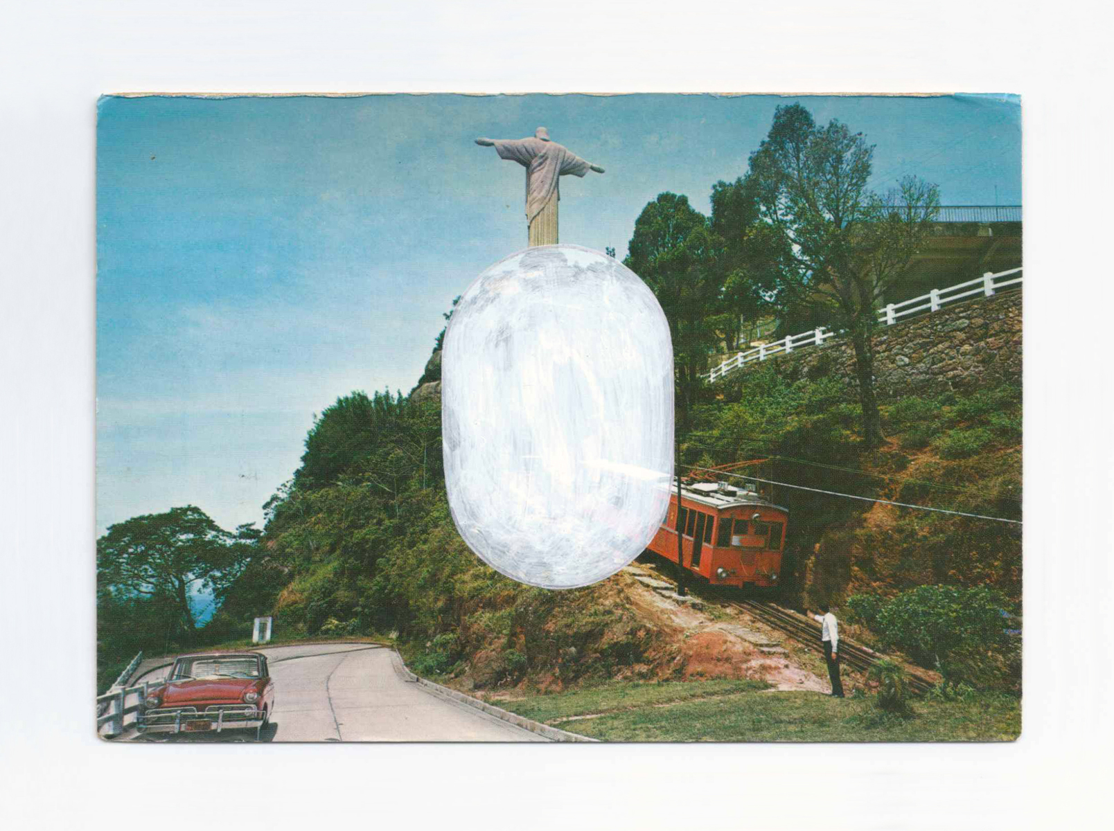 An old postcard of a car, tram, man and Christ statue, plus a white painted oval.