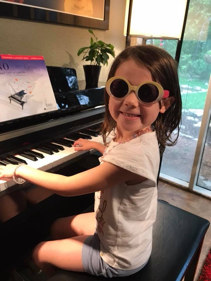 little girl wearing sunglasses and playing the piano
