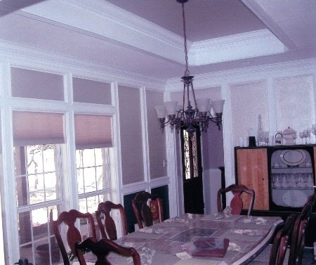 Dining room features Judges paneling with dentil crown molding. Middle raised ceiling is cased with dentil crown molding.