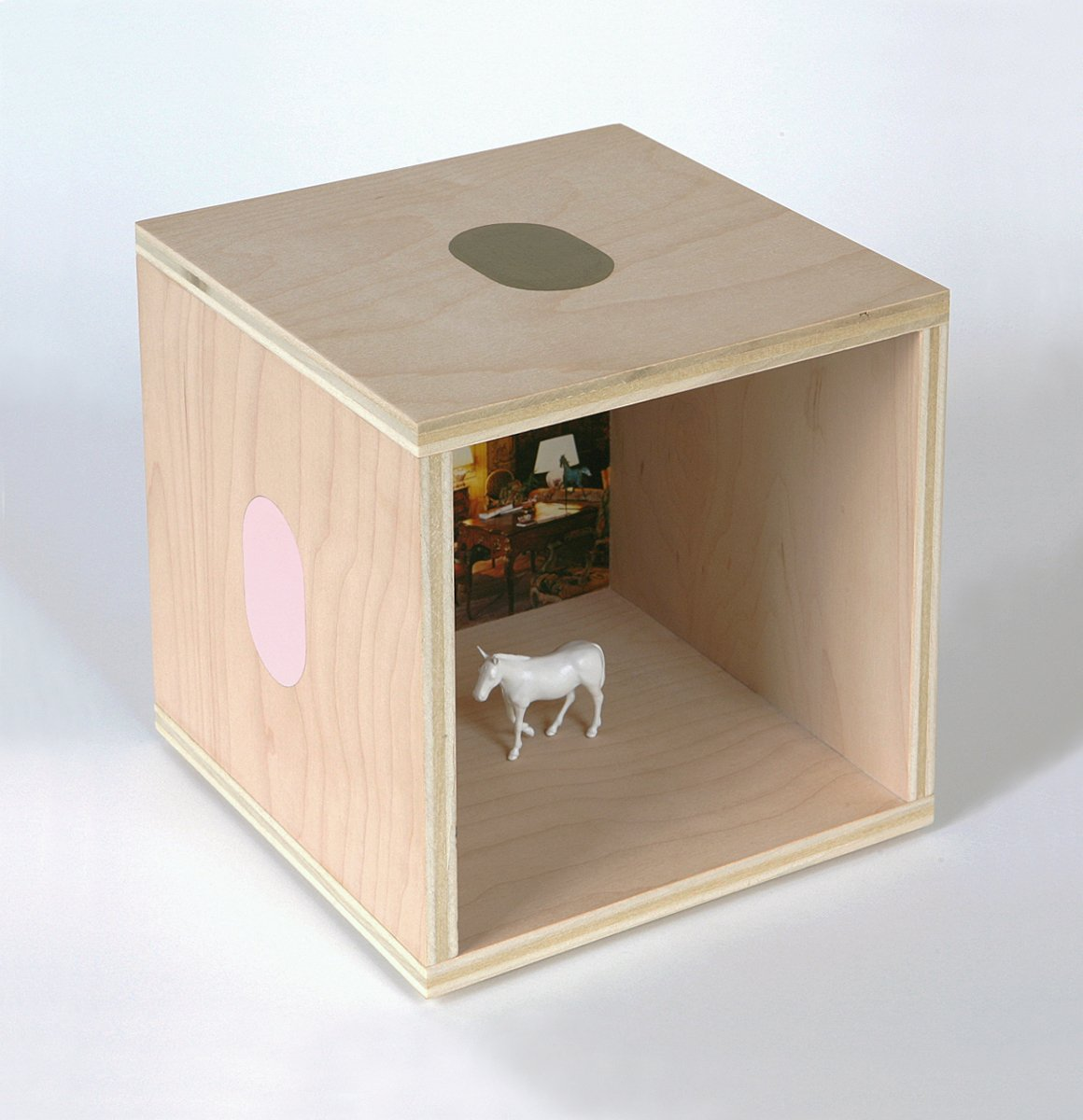 A plywood cube with ovals on the outside and a small white mule model inside.