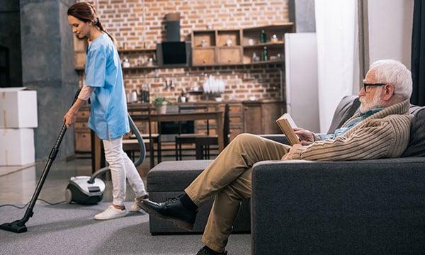 Senior Man Reading while Caregiver Vacuums Room