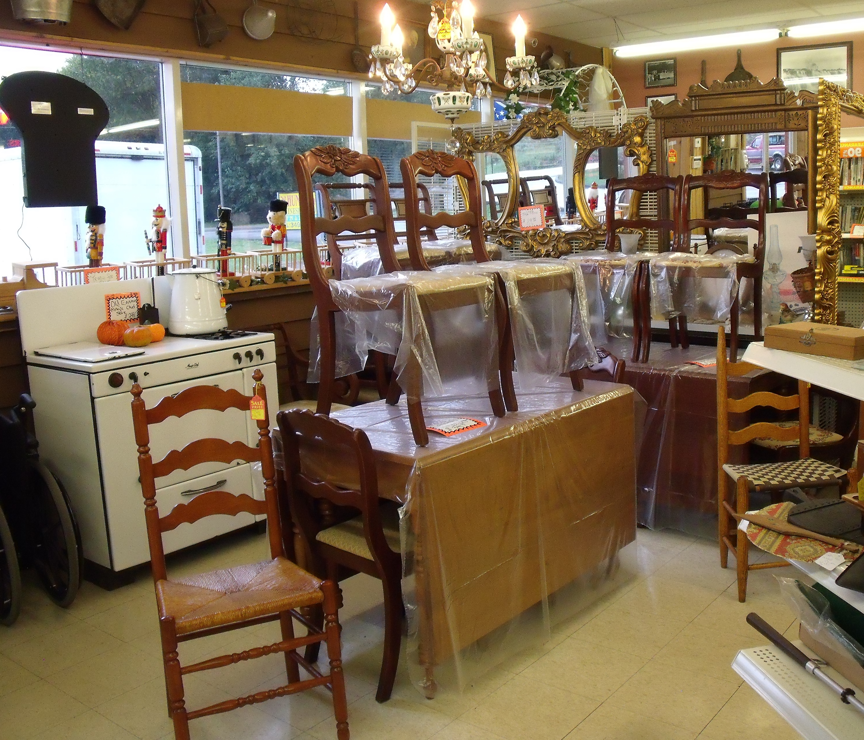 Drop Leaf Tables with Chairs, along with a vintage chandelier, and a few cane bottom chairs.