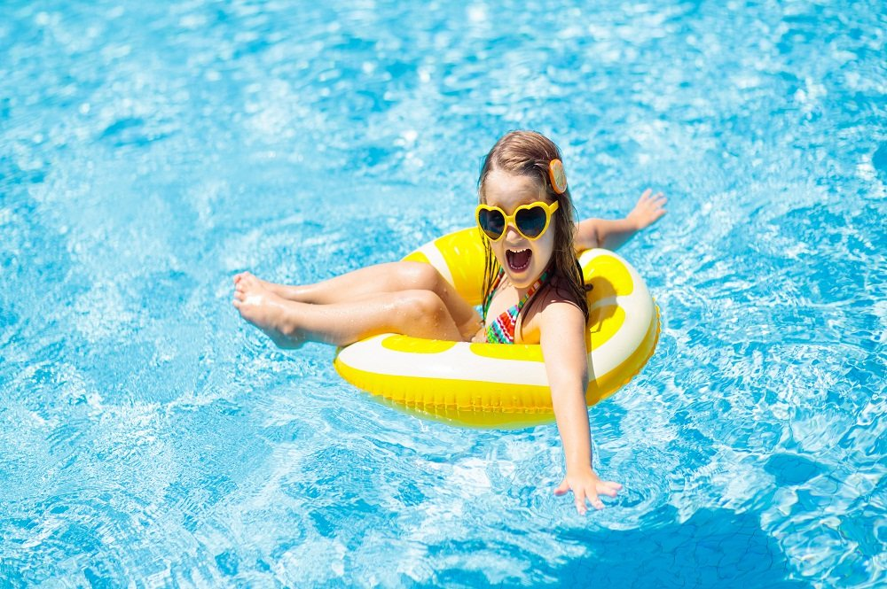 A little girl smiling and floating on a yellow inflatable tube in a residential pool