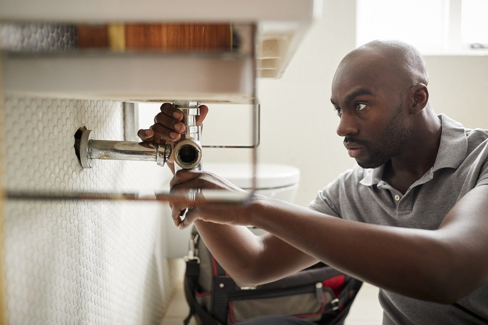 African American Plumber Checking Drain Pipe