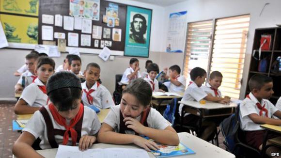 School children in present day Cuba. Government propaganda looms over the classroom.