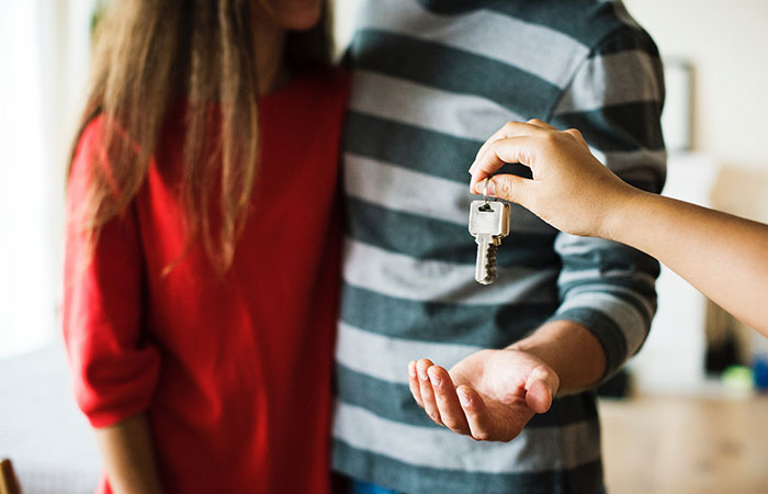 Agent Giving Key to Couple