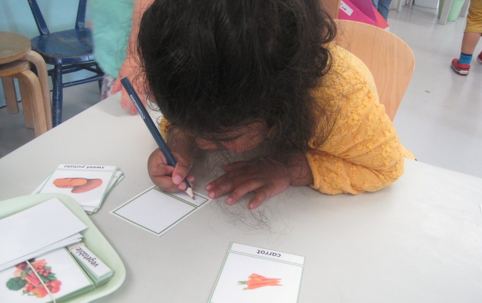 Writing out her own Classified Cards of vegetables.