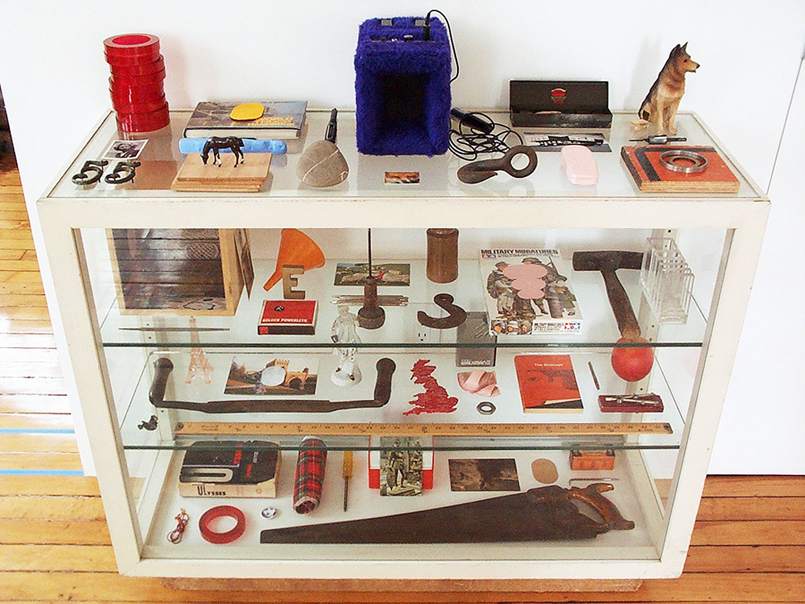 A white display case full of objects including saws, postcards and a dog figurine.