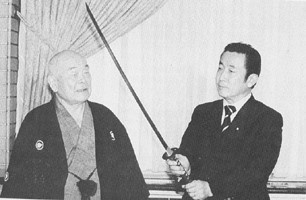 "20 July 1997. Nakamura Taizaburo Sensei presenting a sword to Prime Minister Hashimoto Ryutaro.  PM Hashimoto is a kendo 5th dan.  The sword was forged by a former Yasukuni Shrine smith. The sword is a copy of Yamaoka Tesshu's favorite sword, called ""Sa-Moji""."