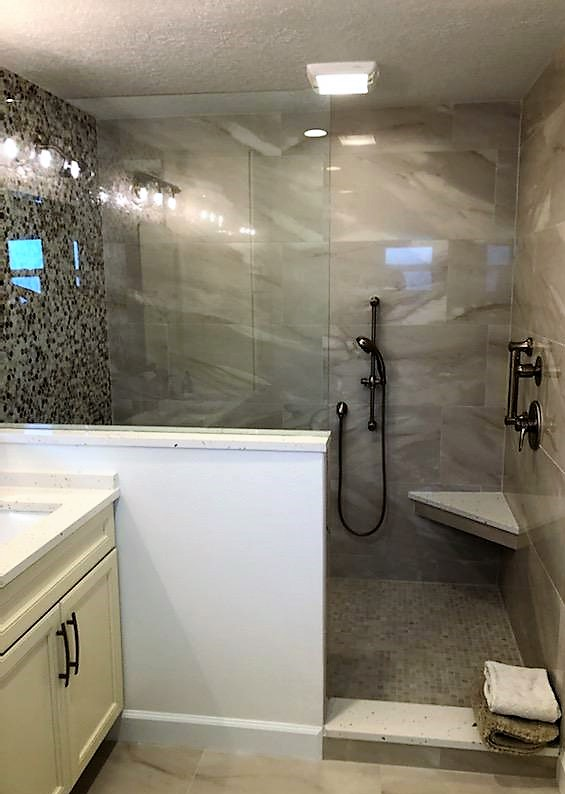 Flawless walk-in shower featuring a  spacious seat with elegant tile work.