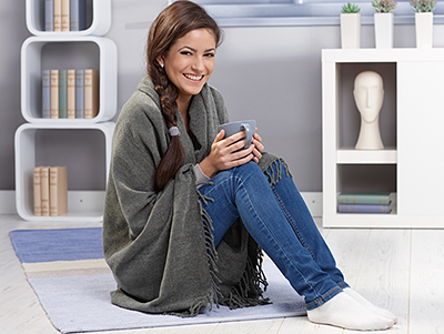 Happy young woman with blanket and tea sitting on floor||||