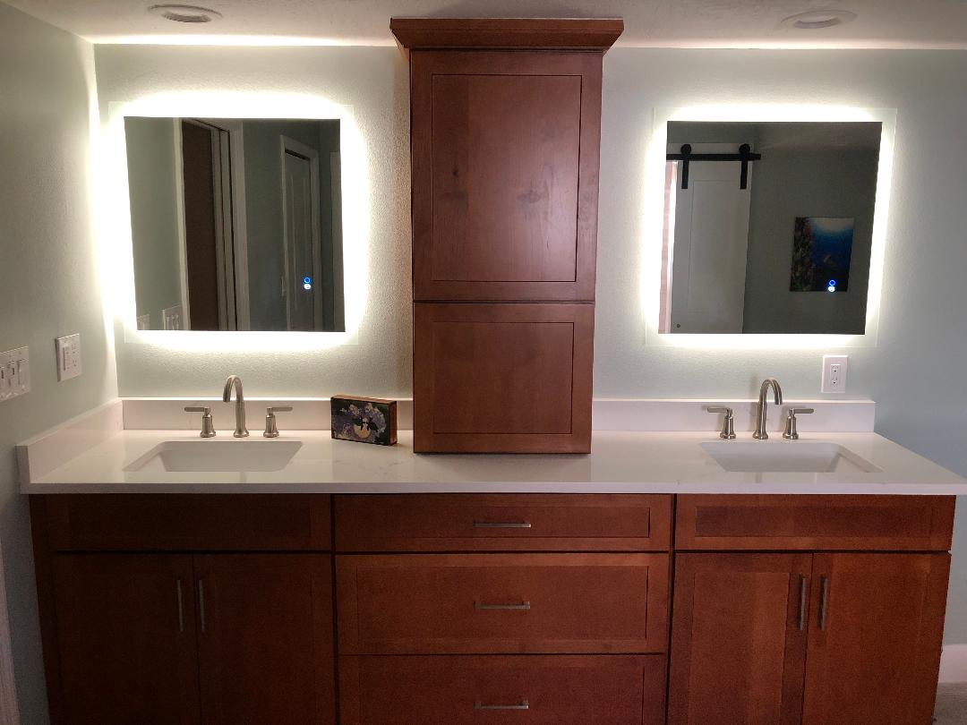 Featuring back lit mirrors with matching tower and dual sinks.