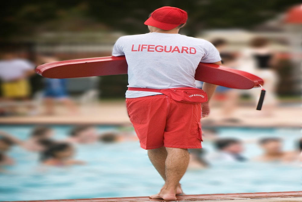 A lifeguard standing on the edge of a public pool and watching the swimmers for signs of distress
