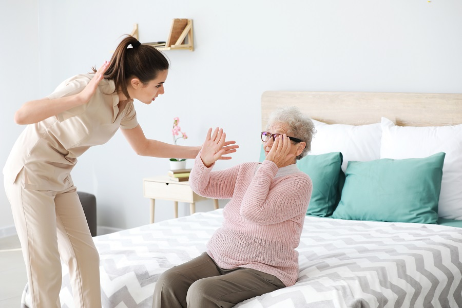 Nurse in Nursing Home Mistreating Elderly Lady Sitting on Bed