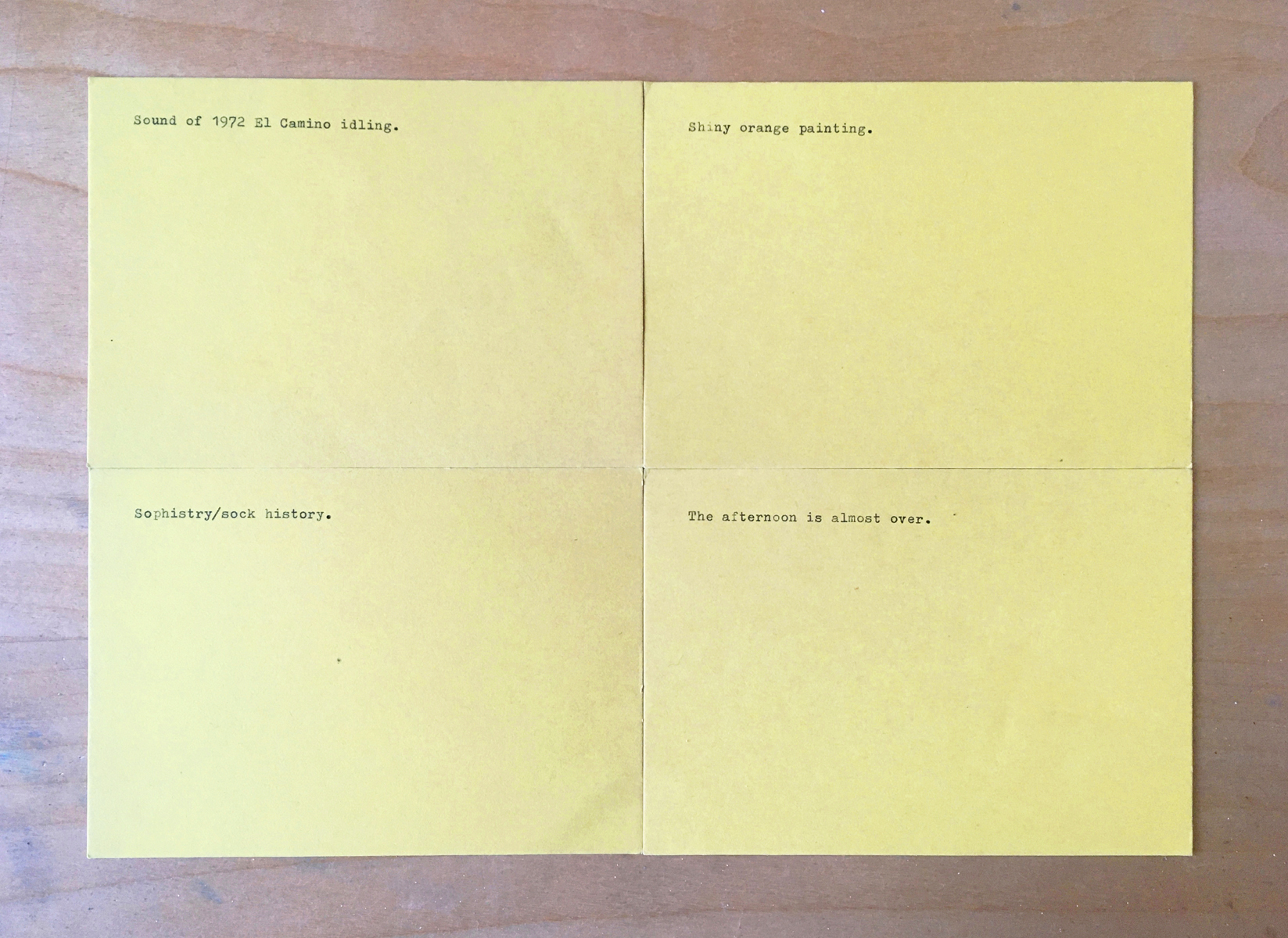 Four yellow index cards, one line is typed on each, placed on a plywood table.