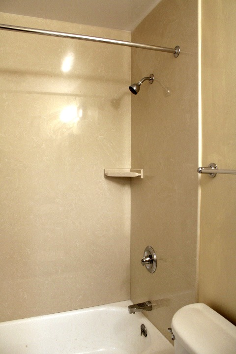 The shower has new marble walls.