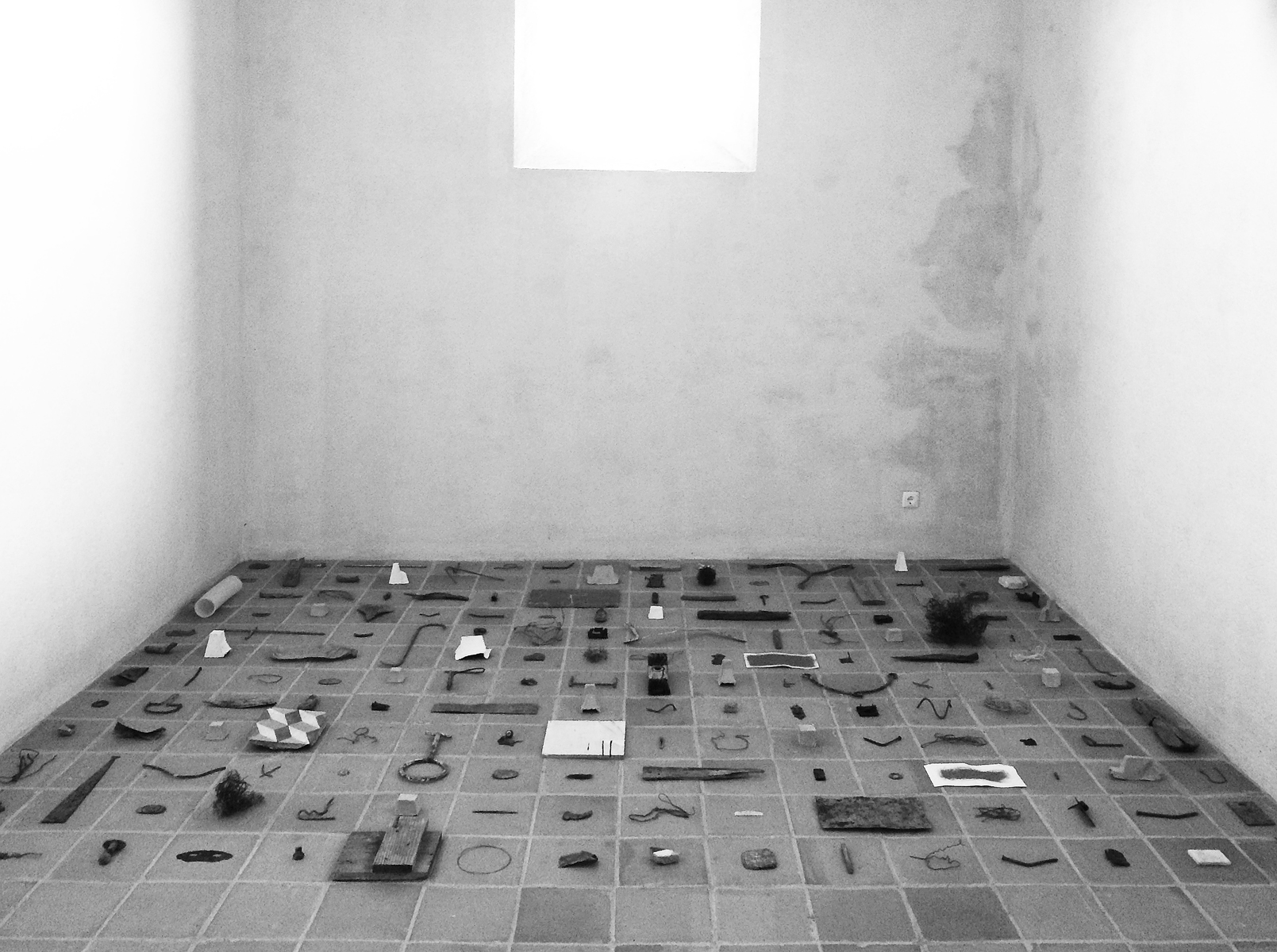 Objects arranged in a grid on a tile floor in an otherwise empty, monastic space.