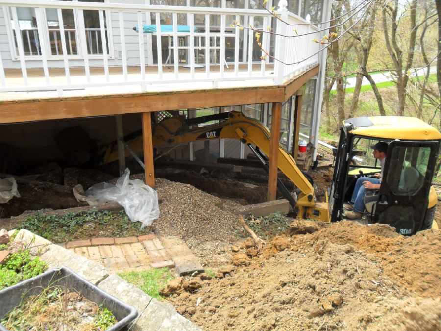 Digging under a house deck to replace a sewer line.