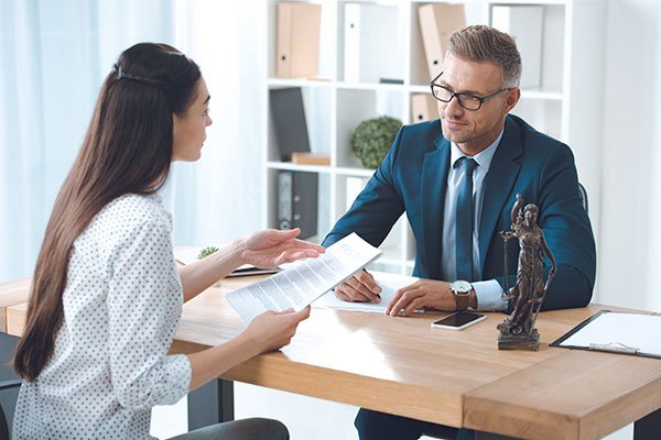 lawyer and client looking at each other while discussing papers in office
