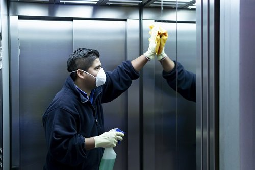 Man Wearing a Mask and Cleaning Elevator