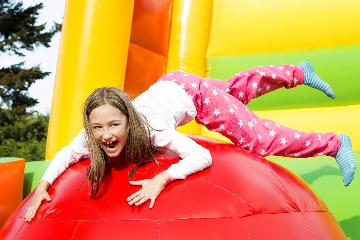 Girl Having Lots Of Fun On A Inflate Castle While Jumping