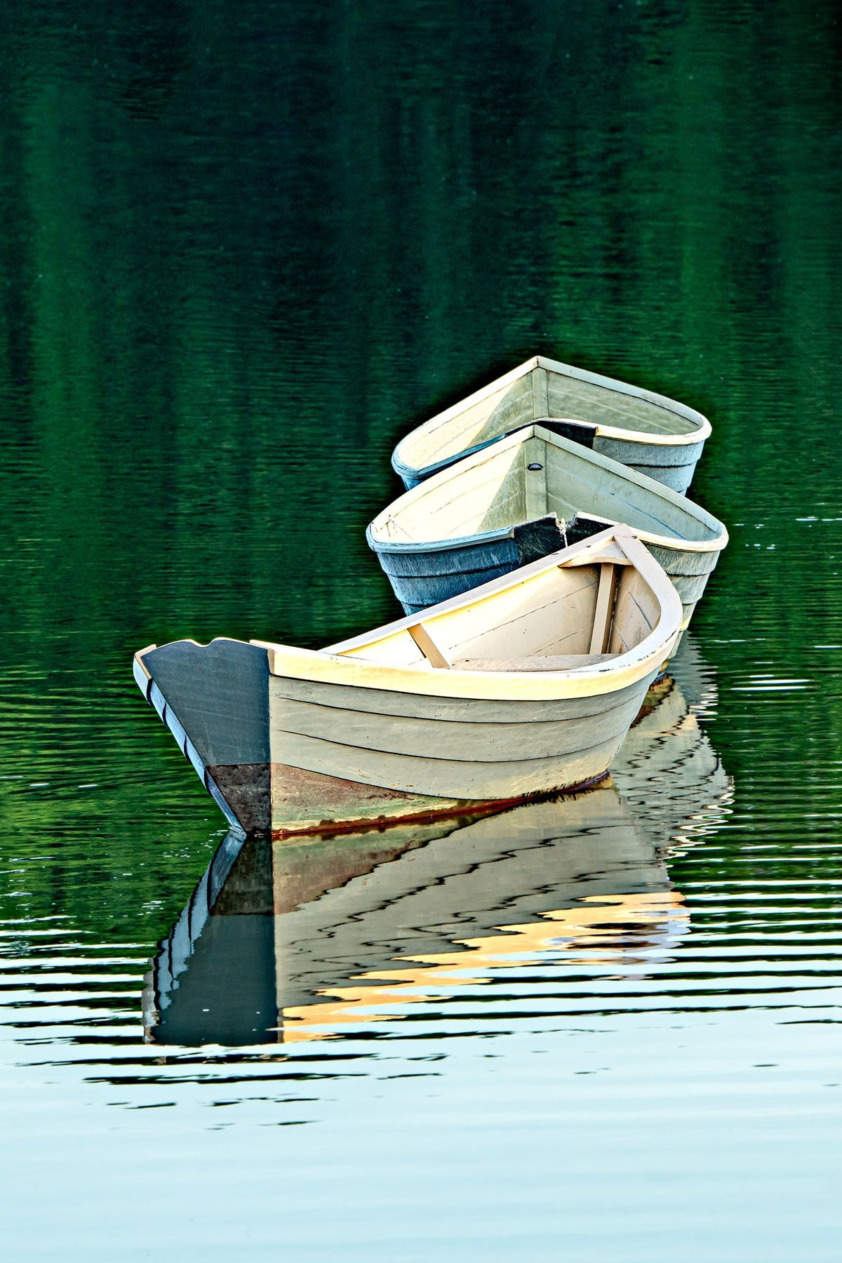 THREE DORIES - These three boats(dories) are anchored in the water in the town of Kennebunkport, Maine. Wind, tide and activity cause them to move constantly. They appear to dance in the water. Light and water level change the show throughout the day. They have become a town icon. This is one of many photos I took while there.
