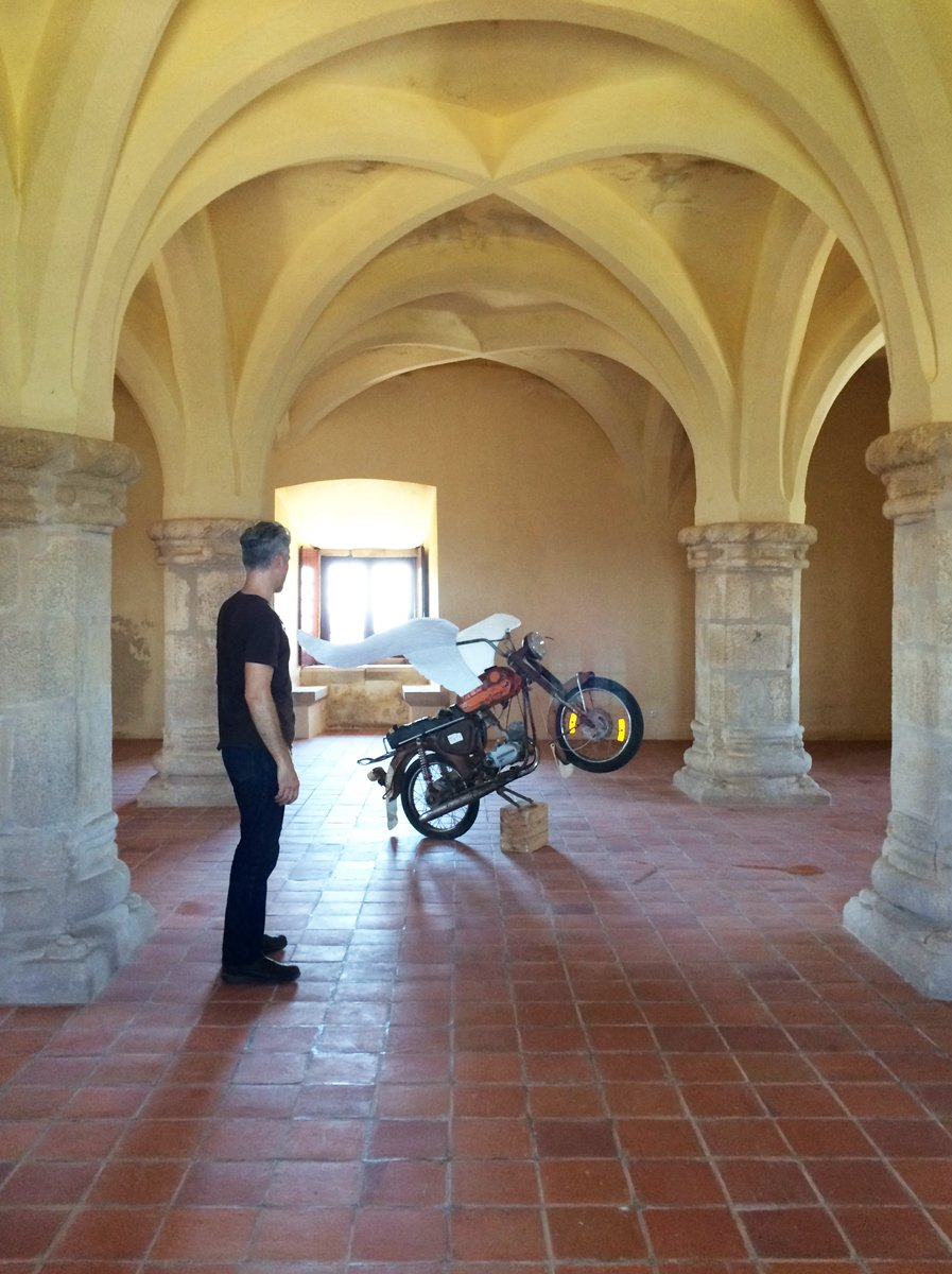 A man and a winged motorcycle in a room with stone pillars and vaulted ceiling.