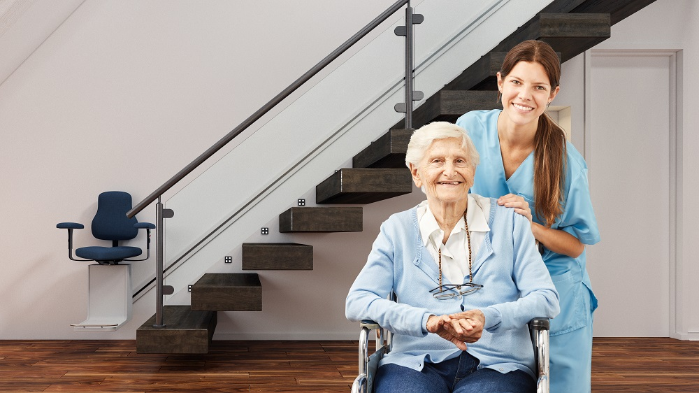 Woman in wheelchair and caretaker in front of stairlift
