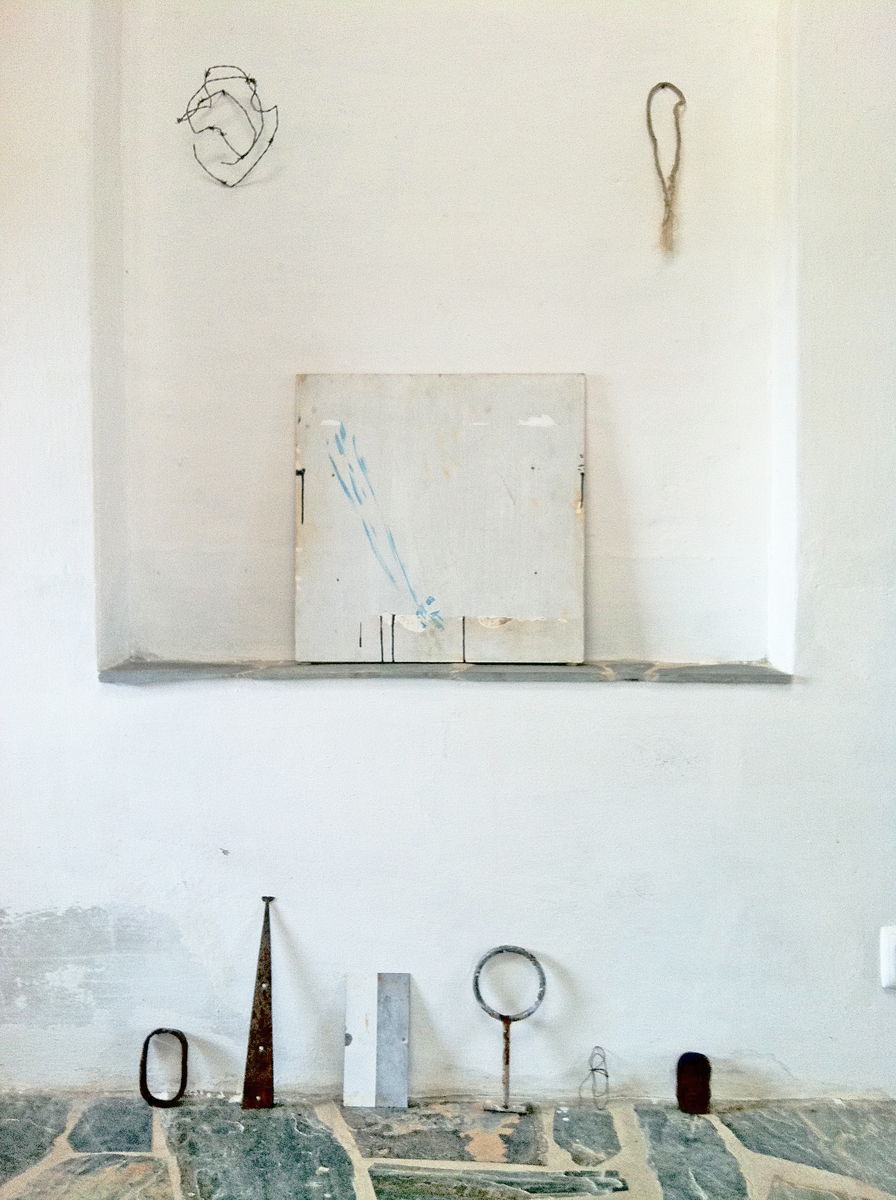Rustic objects and a white painting in a whitewashed space with a stone floor.