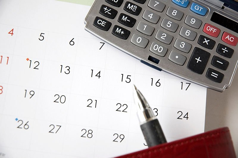 Pen point on calendar with calculator