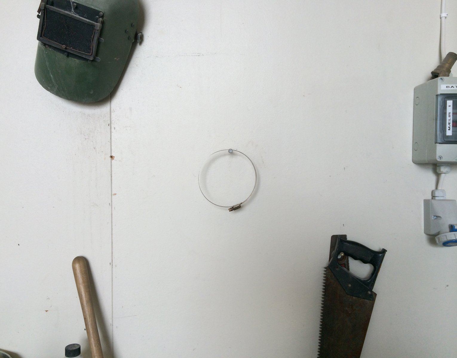 A welders mask, saw and centered circular pipe clamp hang on a white wall.