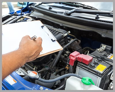 Mechanic Holding Clipboard and Checking the Car