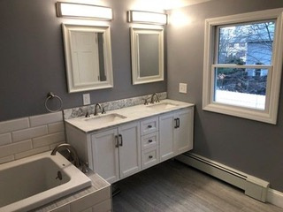 Installed a Anderson high performance double hung window, re-framed all perimeter walls, closed cell insulation, electrical, plumbing, heat element, stone tile floor, and wall hung double sink vanity.