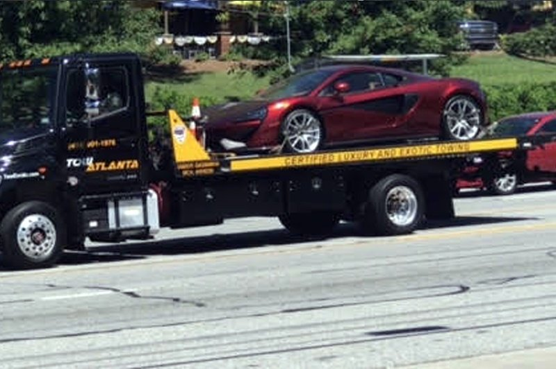 Tow truck hauling a new red car
