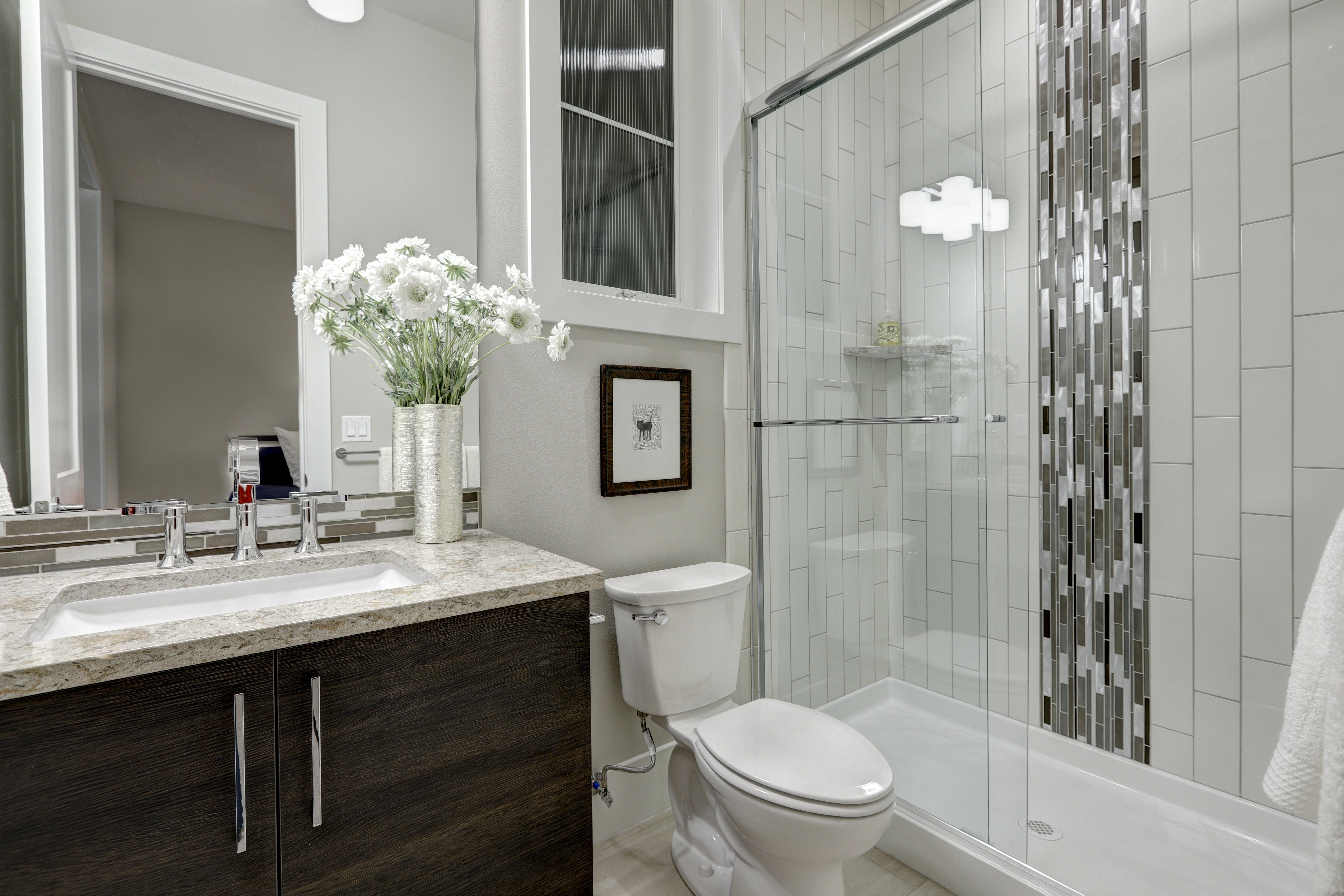 Bathroom Remodel with modern vanity and hardware with quartz countertop and drop mount sink.  Shower includes corner shelving and vertical subway tile with mosaic accent tile in the center.