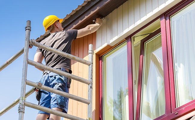 A professional house painter painting the exterior of an East Valley, Arizona area home