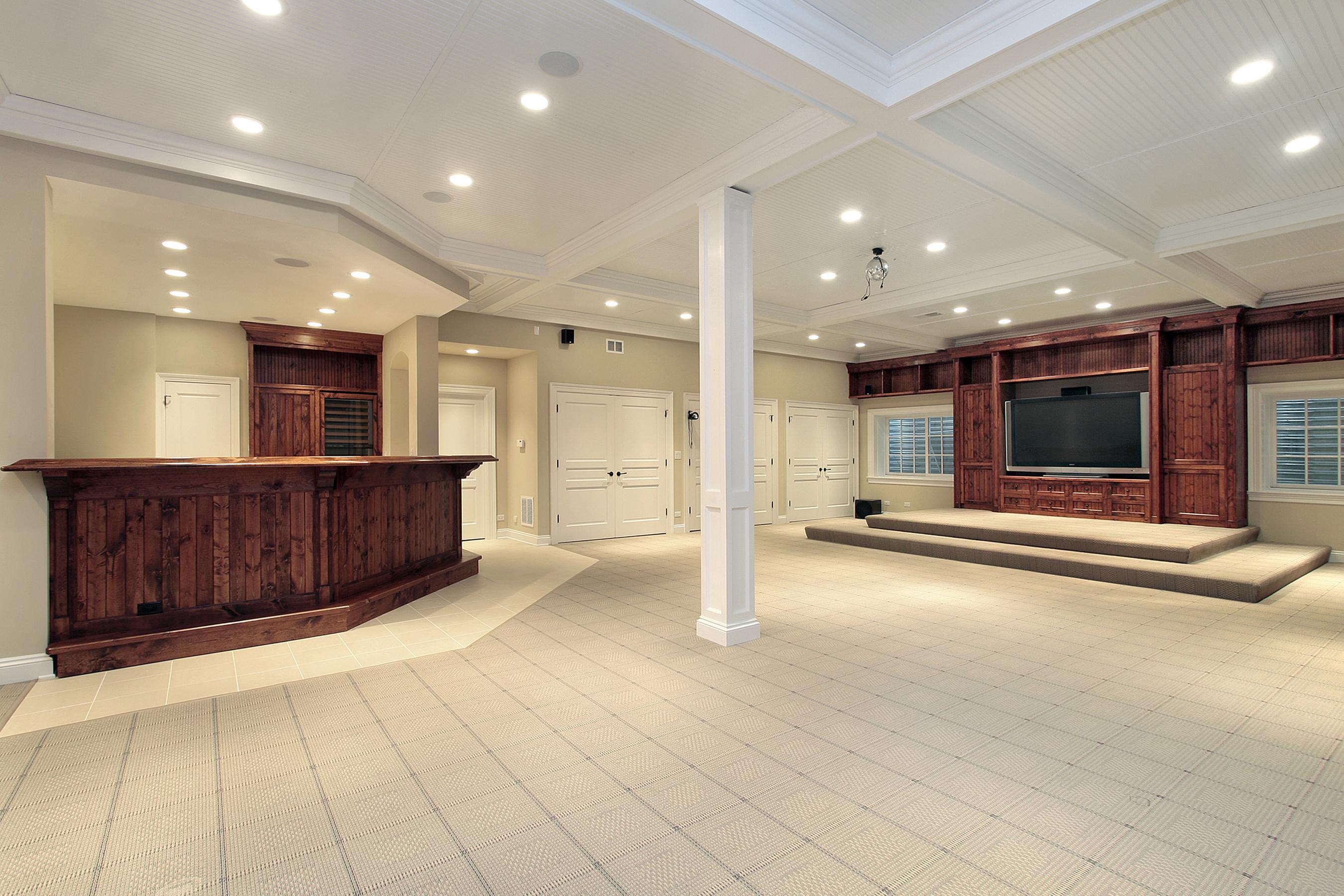 Luxurious basement remodel with hard wood bar, elegant carpet, multi closet storage, large entertainment cabinets and casket ceiling.