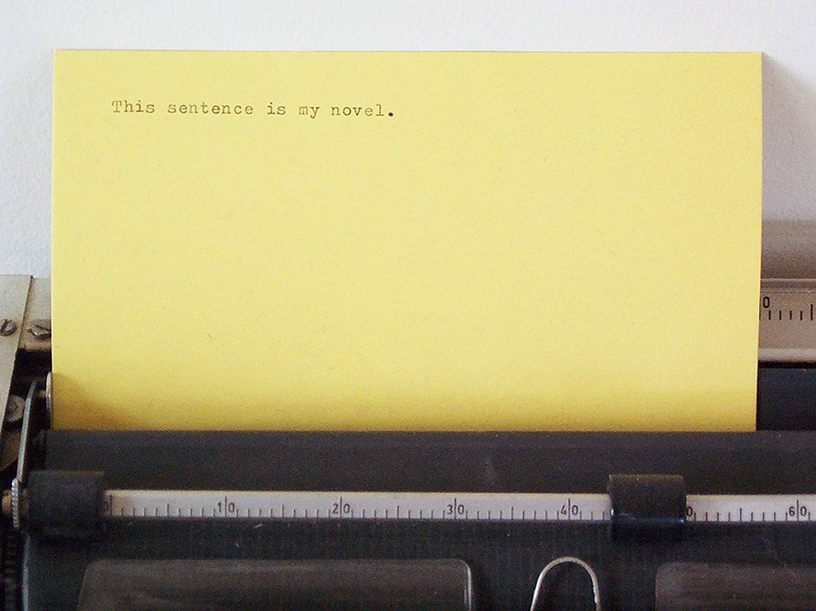 """On a yellow card inserted in a typewriter is typed, """"This sentence is my novel."""""""