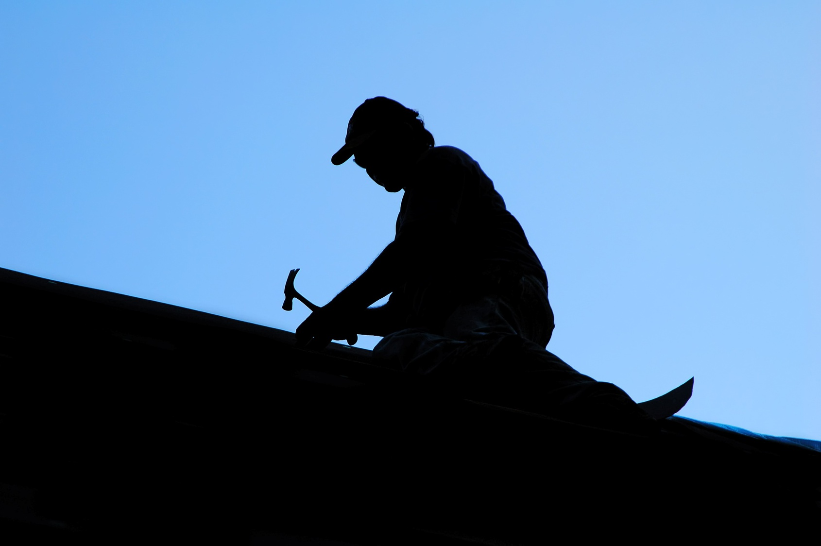 A silhouette of a roofer working a dawn in Alpharetta