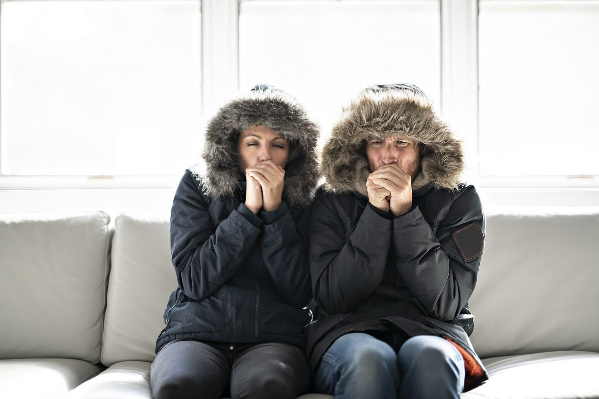 Cold Couple in Coats on Couch